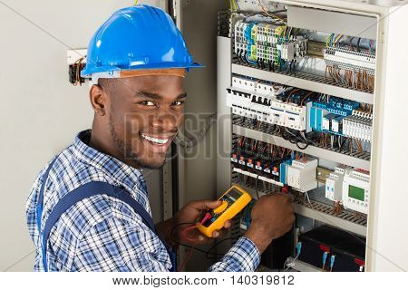 Young African Male Technician Examining Fusebox With Multimeter Probe