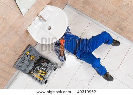 High Angle View Of Male Plumber Repairing Sink In Bathroom