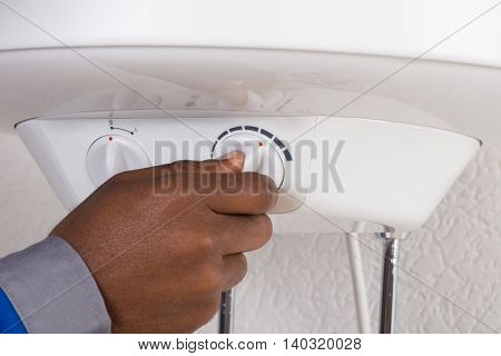 Close-up Of Plumber's Hand Turning The Knob Of Electric Boiler
