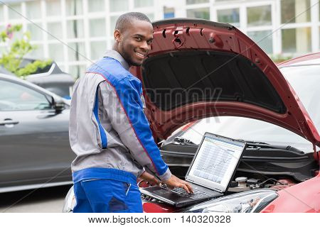 Young Happy Mechanic Using Laptop In Front Of Open Car Engine