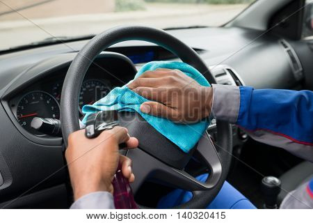 Close-up Of A Male Worker Wiping Steering Wheel With Cloth In Car