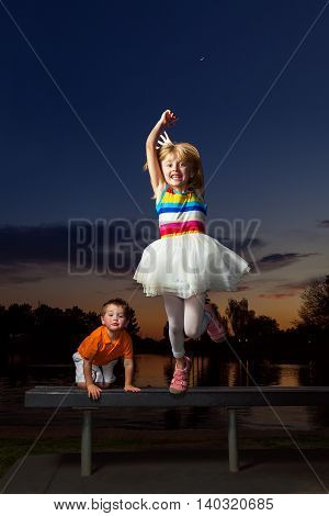 A young blond girl with a big smile jumps off of a bench a sunset. Her little brother climbs up behind her with a funny expression. The girl has her shoes on the wrong feet.