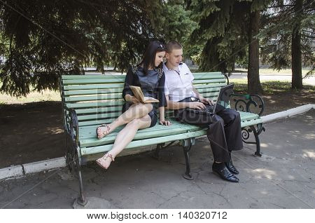 fellow with a girl on a bench in a sunny day