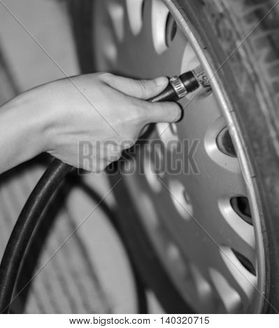 blurred image of filling air into a car tire before driving car