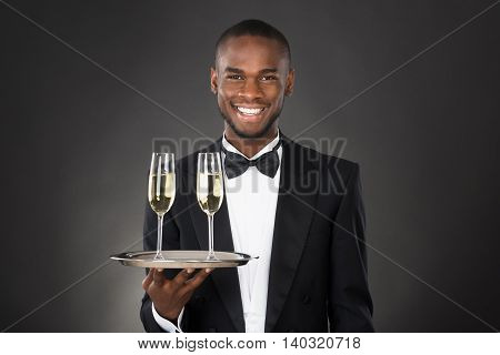 African Waiter Holding Champagne Drink Against Black Background