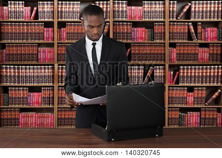 Male Lawyer With Papers And Briefcase At Desk In Office