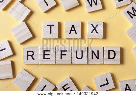 tax refund text on wooden cubes. wood abc at table.