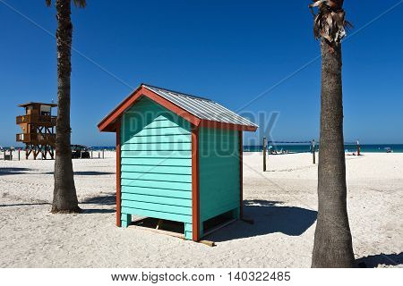 A colorful beach bath house on the sandy public beach area