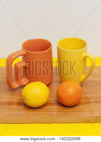 Yellow and orange cups staying near fresh colorful fruits: lemon and mandarin on wooden cutting board. The optimistic source of energy and vitamins after winter.