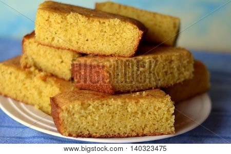 Cornbread squares made with Yellow Cornmeal and Buttermilk. Slices stacked on a white plate. Closeup
