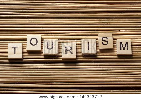 TOURISM word written on wood block at wooden background.