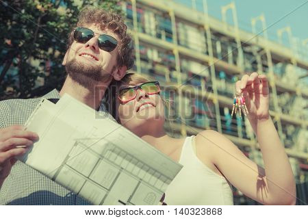 Real estate and family concept - young couple on front of new big modern house with blueprint project and key dreaming about home
