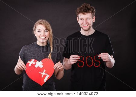 Happy Couple With Plaster Heart And Sos Word.