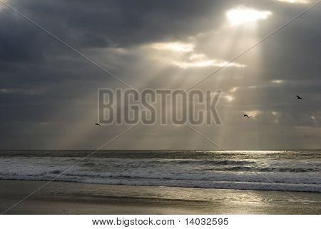 A peaceful beach scene with powerful sun-rays beaming through the clouds.