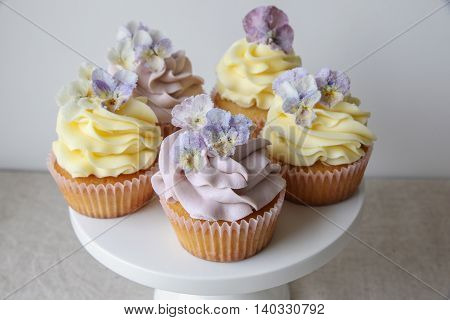 Purple And Yellow Cupcakes With Sugared Edible Flowers On Cake Stand.