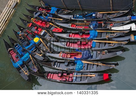 VENICE, ITALY - JULY 3: Gondoliers prepare their Gondolas for the day on a canal in Venice Italy on July 3, 2016.