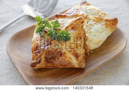 Homemade chicken puff pie on wooden plate