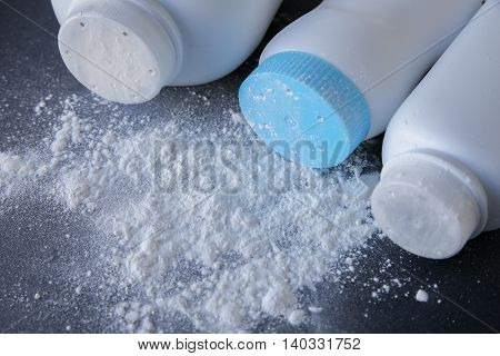 Talcum powder bottles and powder on black background