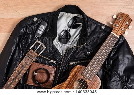 Black jacket with men accessories and ukulele on wooden table still life style