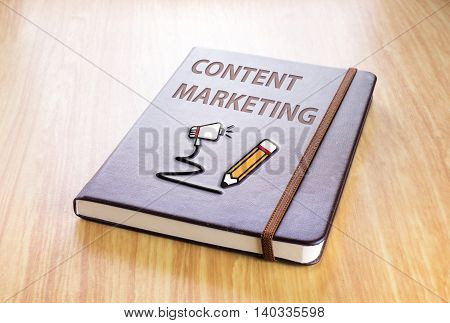 Brown Notebook With Content Marketing Word And Pencil With Speaker Icon On Wood Table, Technology Co
