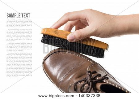 cleaning and polishing brown leather boots over white background