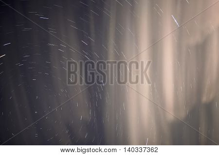 Abstract heavenly background with blurred clouds in the form of nebulae and stars in the form of tracks taken with a long exposure