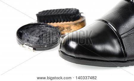 cleaning and polishing black leather boots over white background