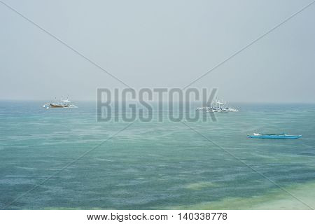 Philippine boats on the calm sea surface at rain season under grey cloudy sky while raining.