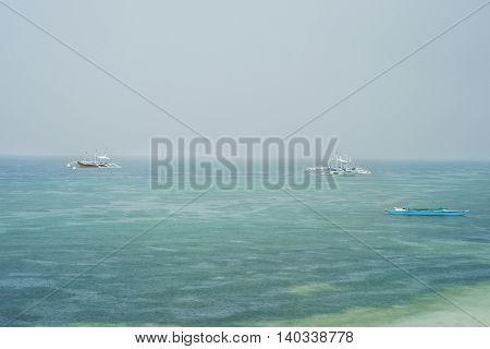 Philippine boats on the calm sea surface at rain season under grey cloudy sky while raining.