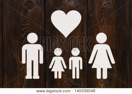 Paper family parents and two clildren. Wooden background. Abstract conceptual image