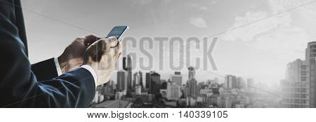 Businessman using mobile phone with panoramic cityscape in business district in the city at sunrise