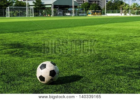 Old soccer ball on green grass at sports school