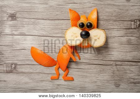 Squirrel made of banana and orange on wooden board