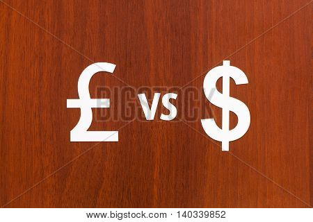 Paper currency signs Pound Sterling VS Dollar. Abstract conceptual image. Wooden background