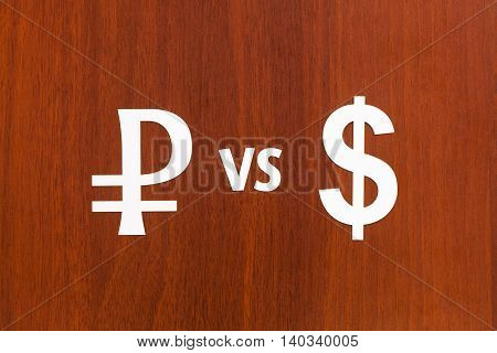 Paper currency signs Rouble VS Dollar. Abstract conceptual image. Wooden background