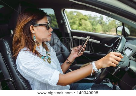 Asian woman looking at a smartphone in the car.
