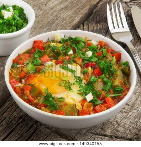 Shakshuka with egg in white bowl on table surface close up. Healthy food