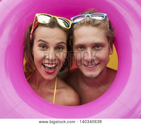 Funny young happy beach couple smiling isolated in the middle of pink inflatable ring