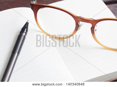 Pen and glasses on the pocket notebook before record something