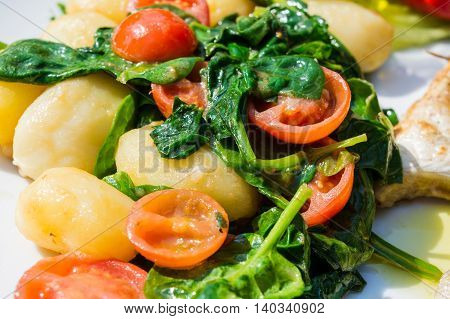 Vegetarian food potatoes with spinach and tomatoes.