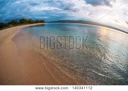 Sandy beach with pattern on the surface at sunset