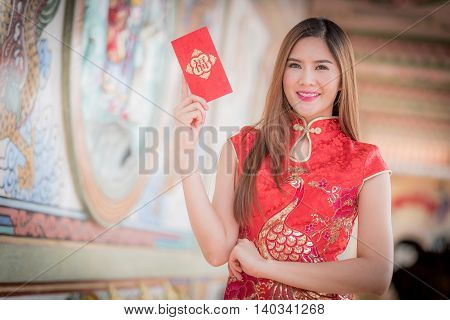 Asian Woman In Chinese Dress Holding Couplet 'happy.' (chinese Word) With Chinese Temple Background.
