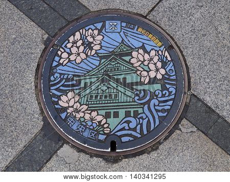 OSAKA, JAPAN - JUNE 07, 2016: A manhole cover in Osaka, Japan. The Osaka castle and sakura engraved on to a manhole cover as a symbol of an important city's landmark.