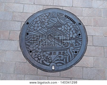 OSAKA, JAPAN - JUNE 08, 2016: A manhole cover in Osaka, Japan. The Osaka castle and sakura engraved on to a manhole cover as a symbol of an important city's landmark.
