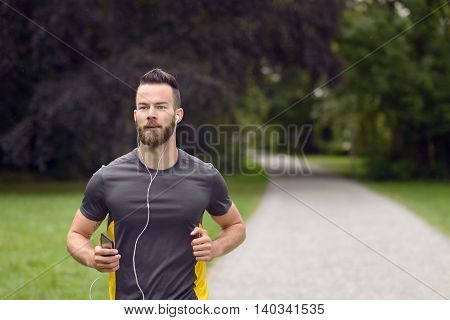 Fit Bearded Young Man Jogging Through A Park