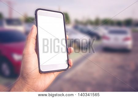 Smart phone with white screen in hand on blurred Parking background