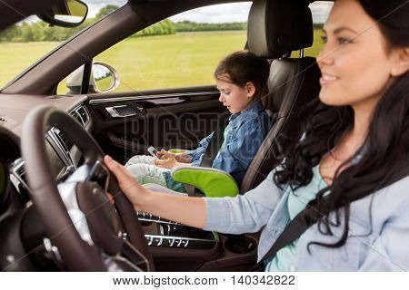 family, transport, road trip, travel and people concept - happy woman and little daughter with smartphone driving in car