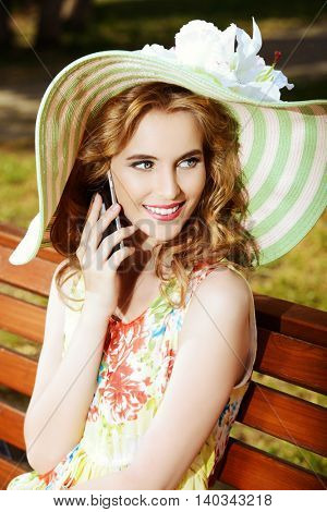 Pretty smiling girl is talking on the phone sitting on a bench in the park. Summer sunny day. Holiday.