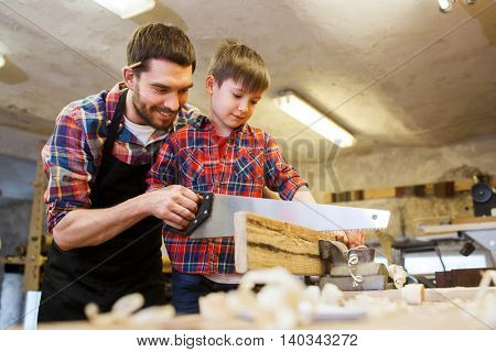 family, carpentry, woodwork and people concept - father and little son with saw sawing wood plank at workshop