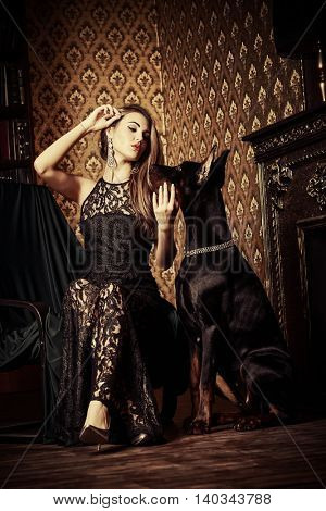 Charming young woman with her dog in a room with luxurious classic interior. Fashion.